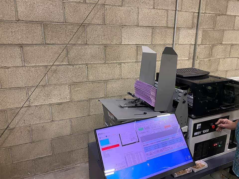 An ES & S machine scans ballot envelopes to match signatures to the registered voter on file (through a barcode). (GV Wire/David Taub)