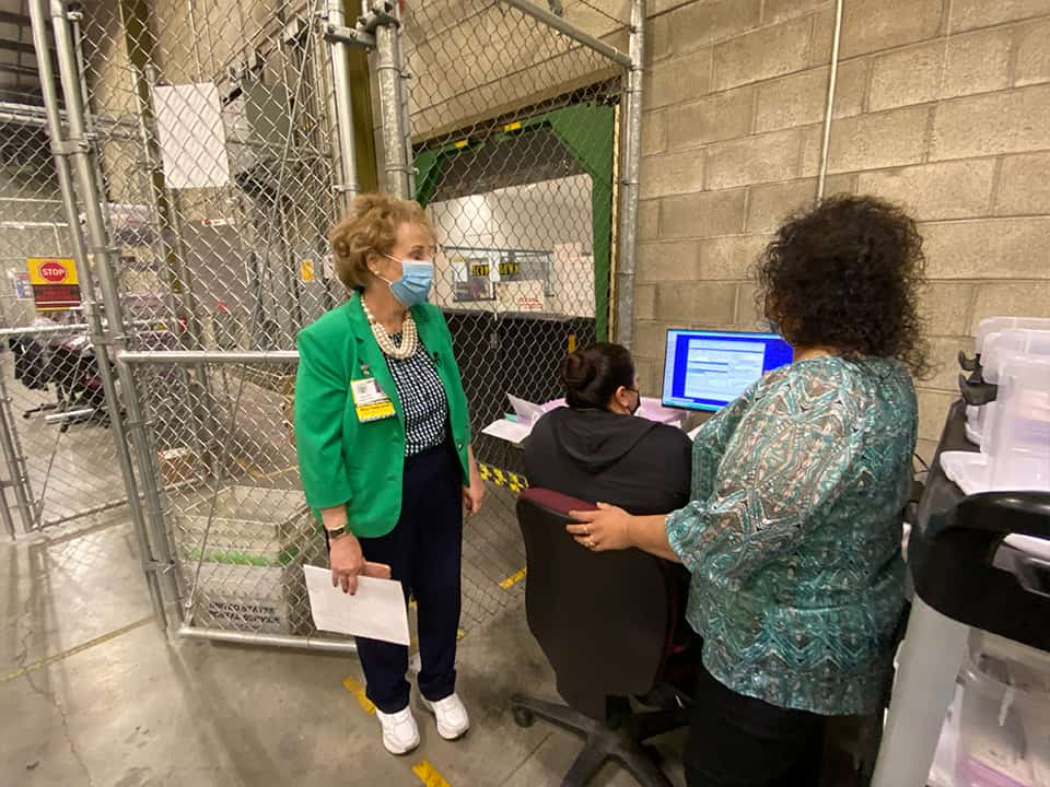 Fresno County Registrar of Voters Brandi Orth (left) and Nysen Armenta, program coordinator, oversee a manual verification of a signature. If the computer scan cannot determine a match, staff will make a visual check. (GV Wire/David Taub)