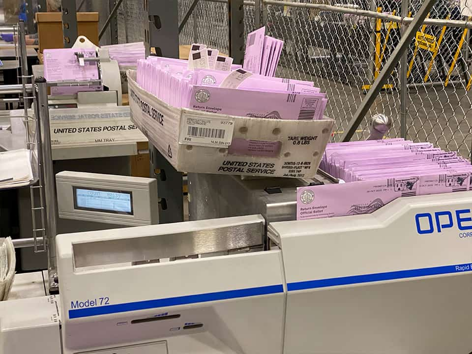 A machine opens the envelopes and removes the ballots. (GV Wire/David Taub)
