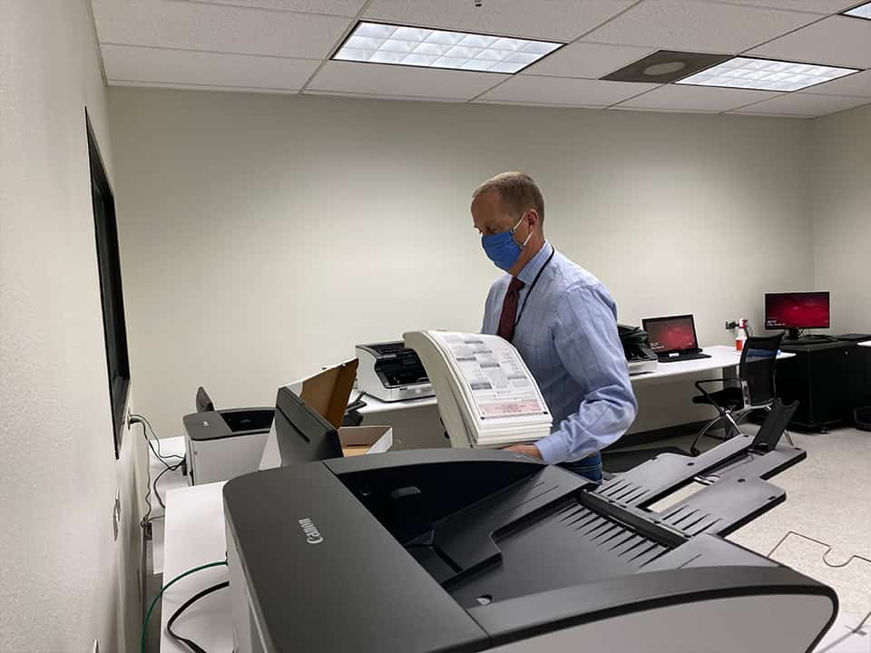 The boxes are taken to a secure room, opened, and placed in a scanning machine. Raymond Beye is one of five employees to have access to the room. (GV Wire/David Taub)