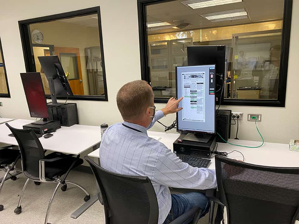 If there are any errors in the ballot, such as a bubble not filled correctly or a write-in candidate not easily read, Raymond Beye inspects the scan manually. (GV Wire/David Taub)