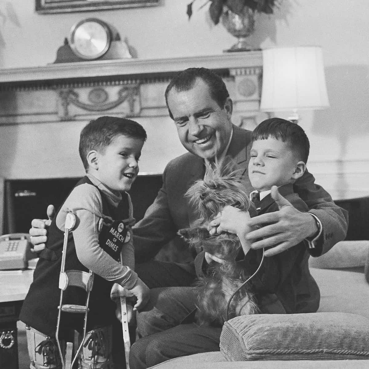 FILE – In this Feb. 5, 1969, file photo President Richard Nixon smiles as he shows off one of the White House pets tiny Yorkshire terrier Pasha to two junior visitors in his office in Washington. His guests are five-year-old Tracy Greenwood, the March of Dimes National Poster Child, and his 7-year-old brother Jamie. (AP Photo, File)