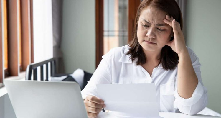 Photo of a woman contemplating how to pay her bills